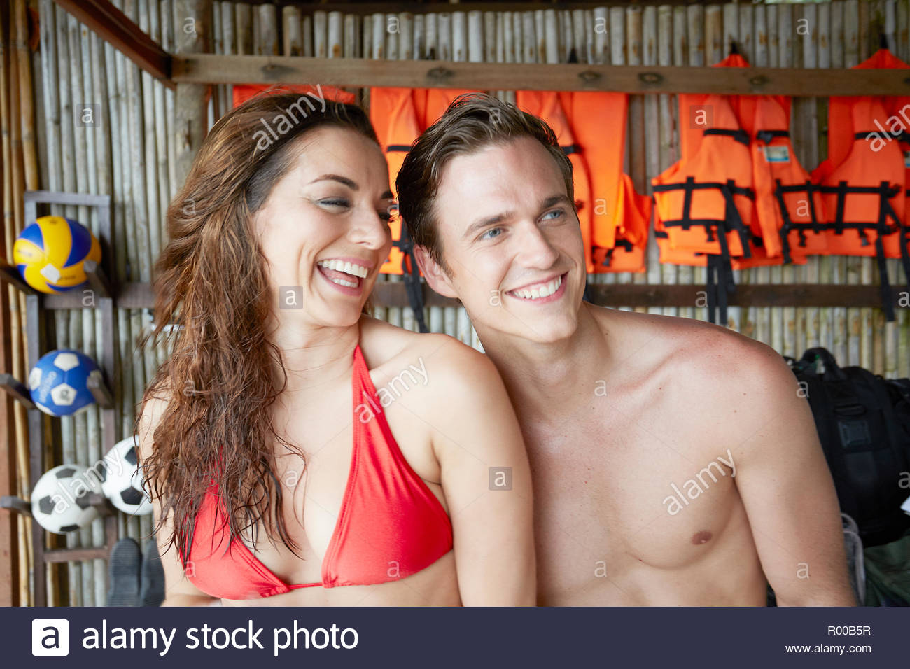 Young couple smiling in front of hanging life jackets - Stock Image