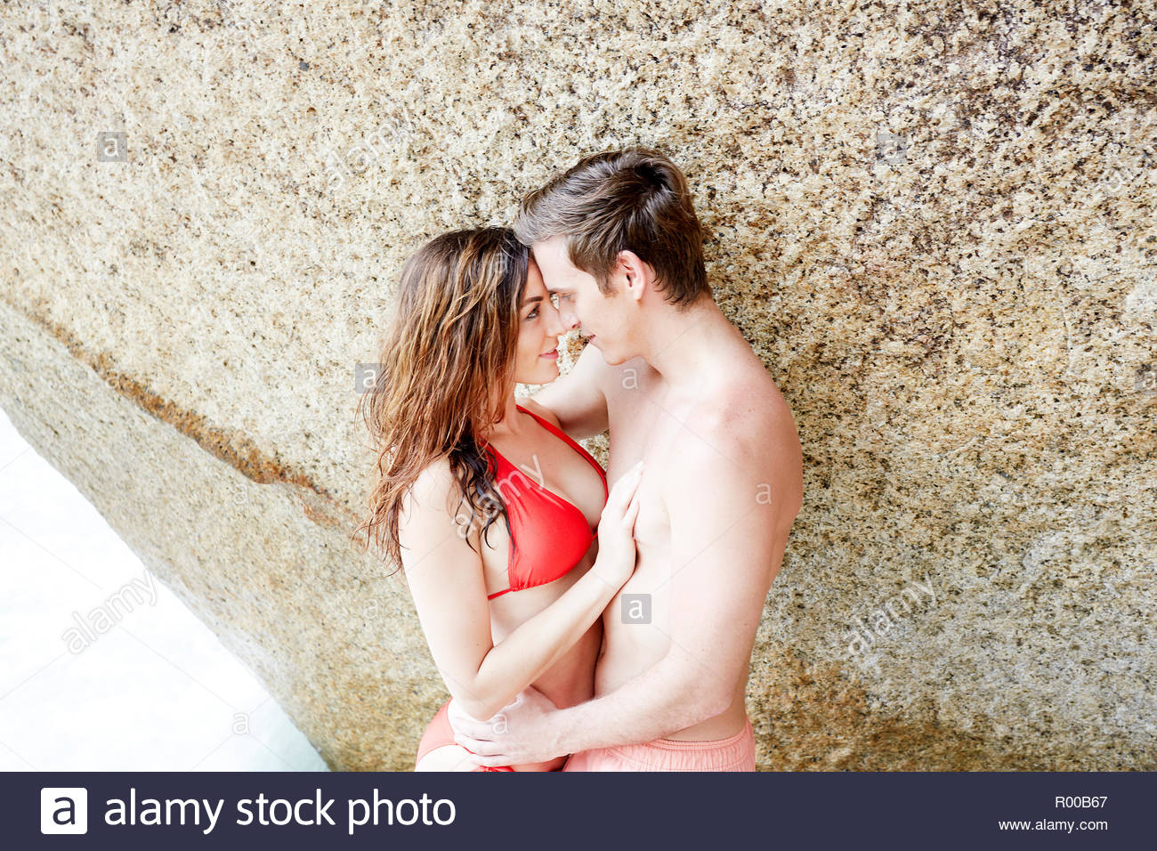 Young couple embracing by boulder on beach - Stock Image