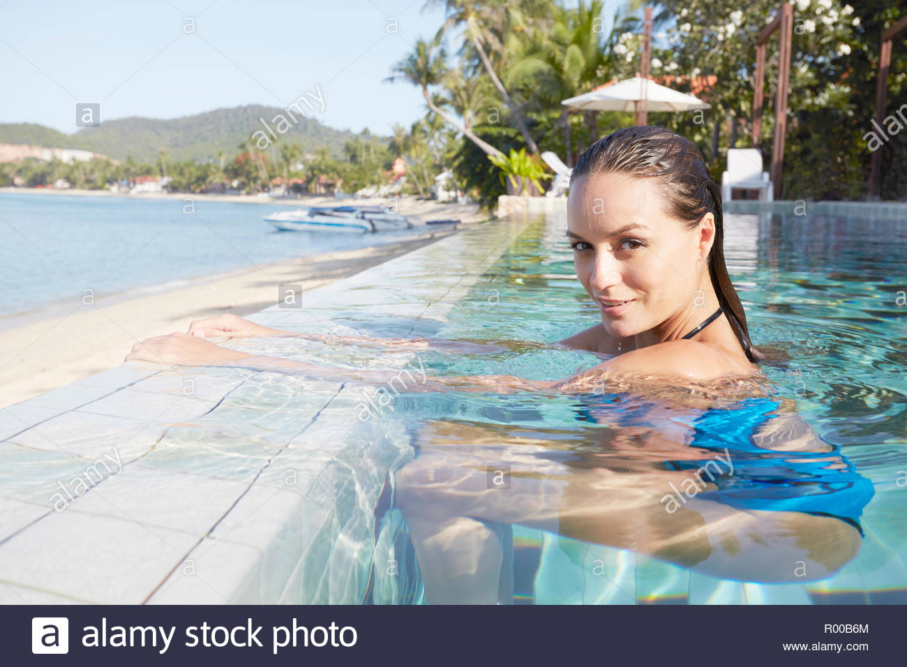 Young woman in swimming pool by beach Stock Photo