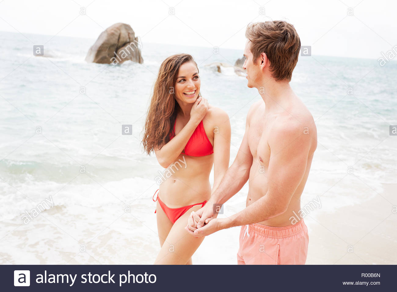 Young couple wearing swimwear walking on beach Stock Photo