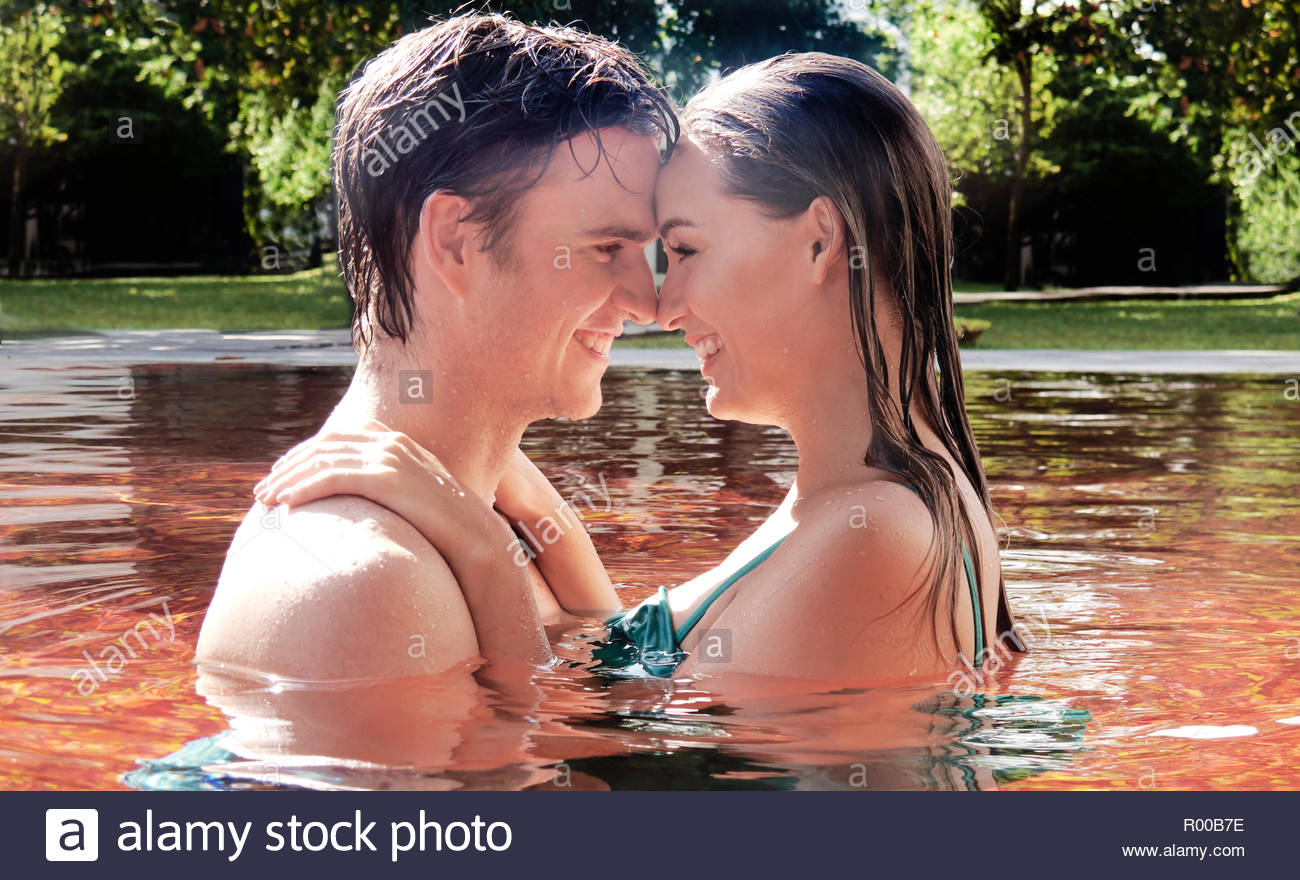 Young couple embracing in orange swimming pool Stock Photo