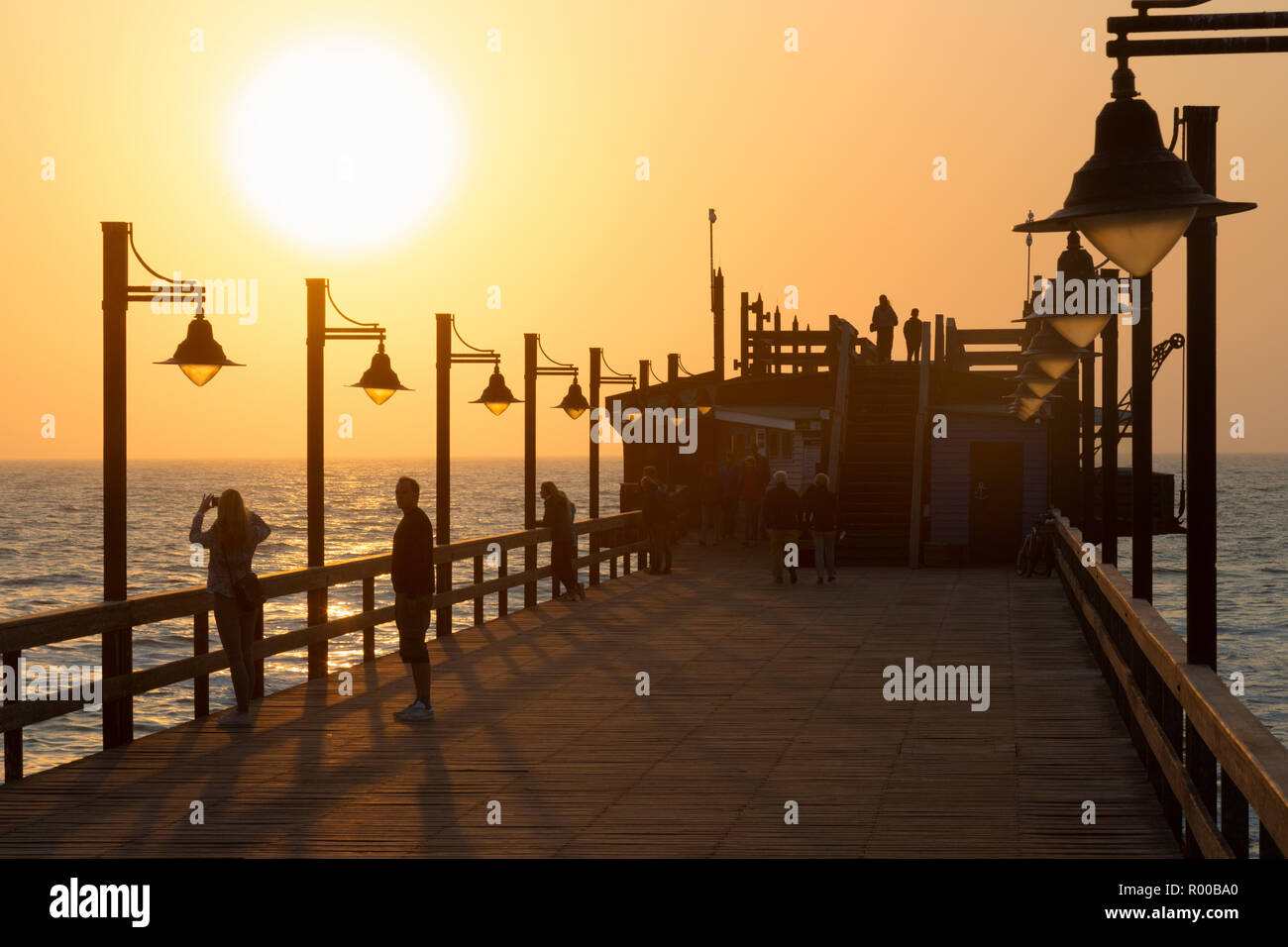 Namibia sunset - tourists on the jetty, Swakopmund, Namibia Africa - Stock Image