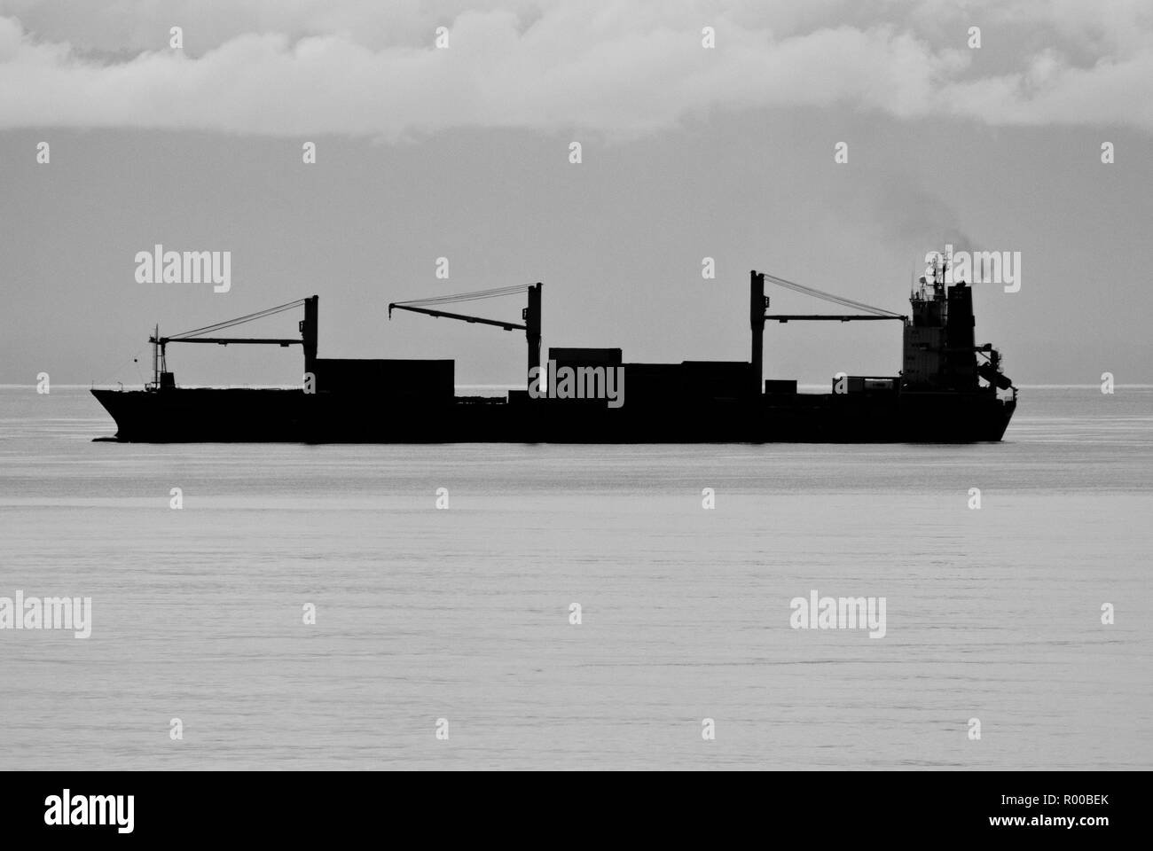 Silhouette of Cargo Ship (Freighter) at Sea - Stock Image