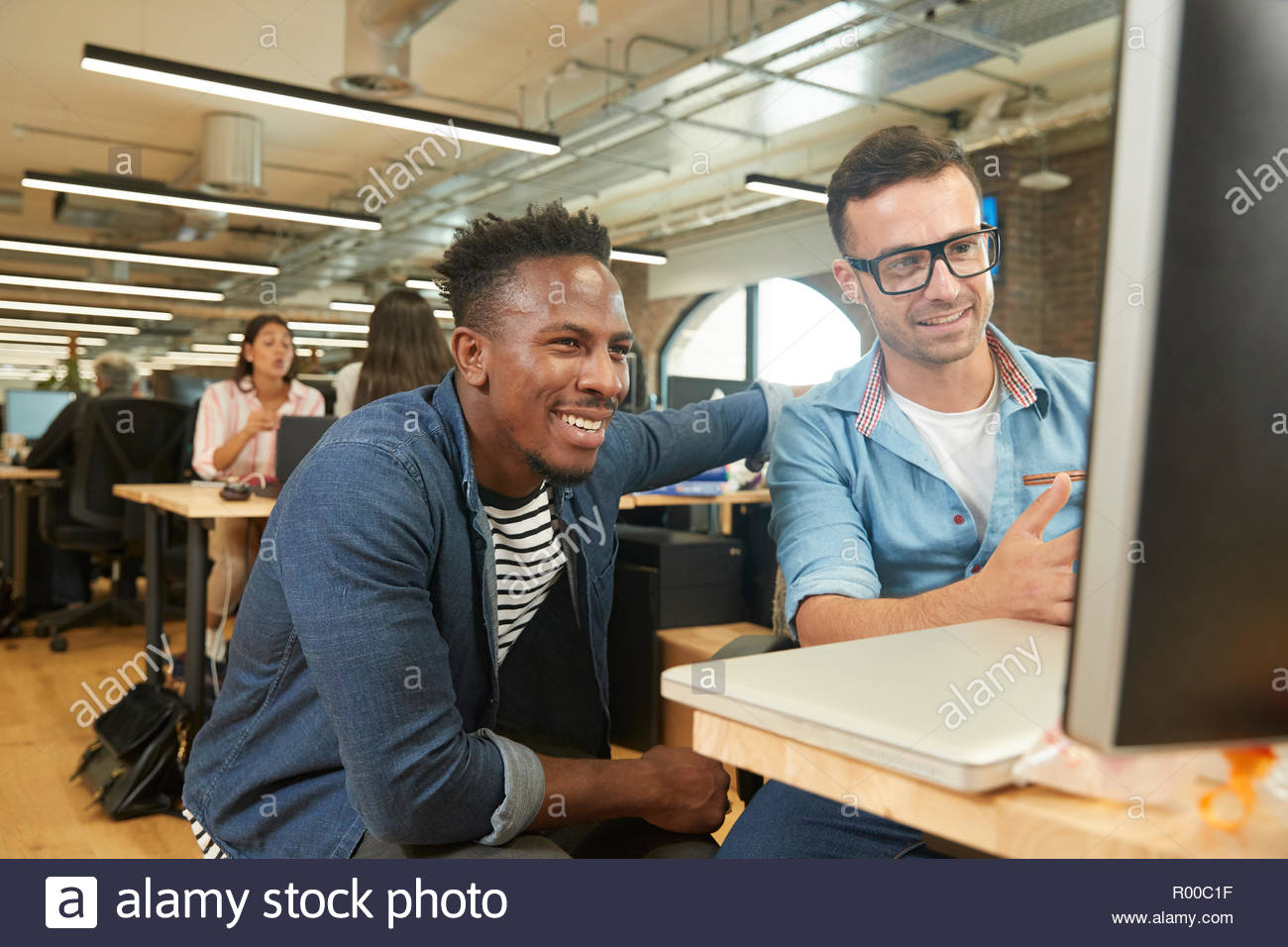 Smiling colleagues using computer Stock Photo
