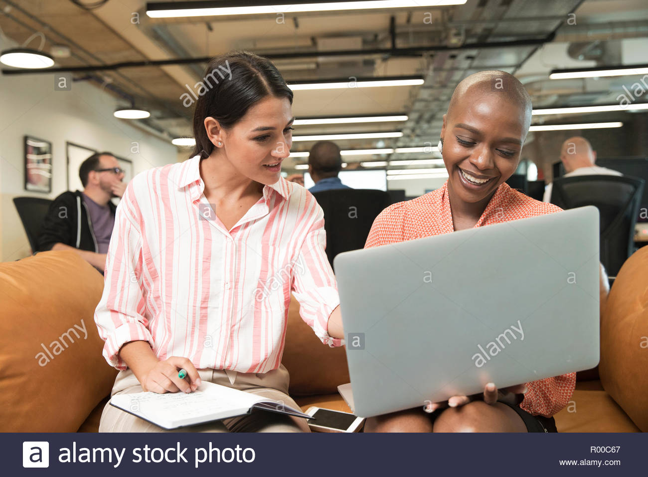 Businesswomen using laptop on sofa Stock Photo