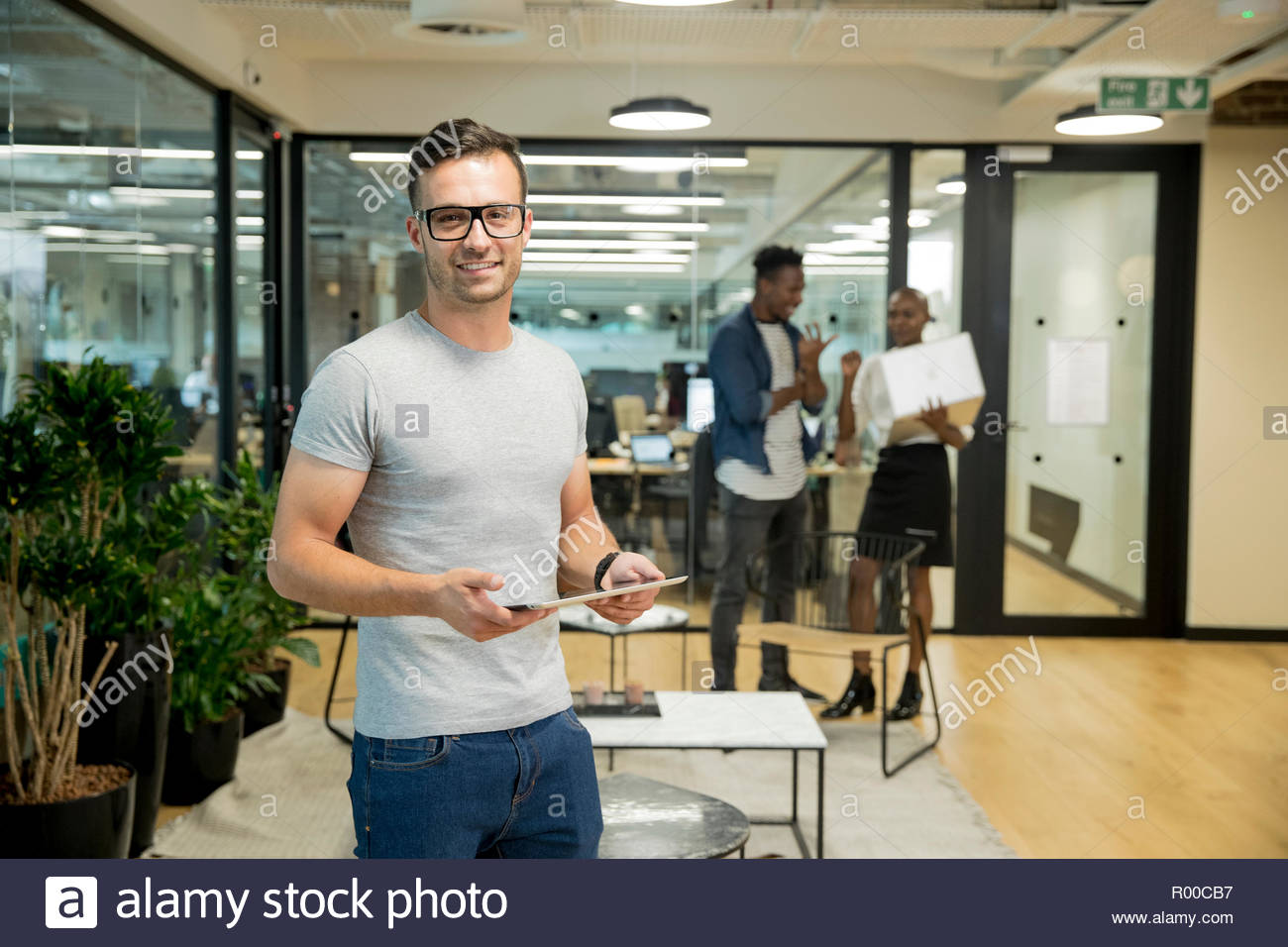 Smiling young businessman holding tablet in office Stock Photo