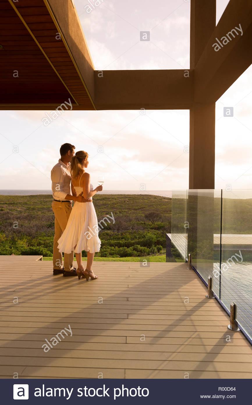 Couple holding white wine on balcony - Stock Image