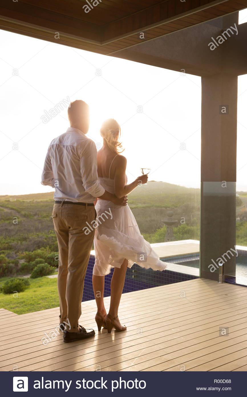 Couple holding white wine on balcony Stock Photo
