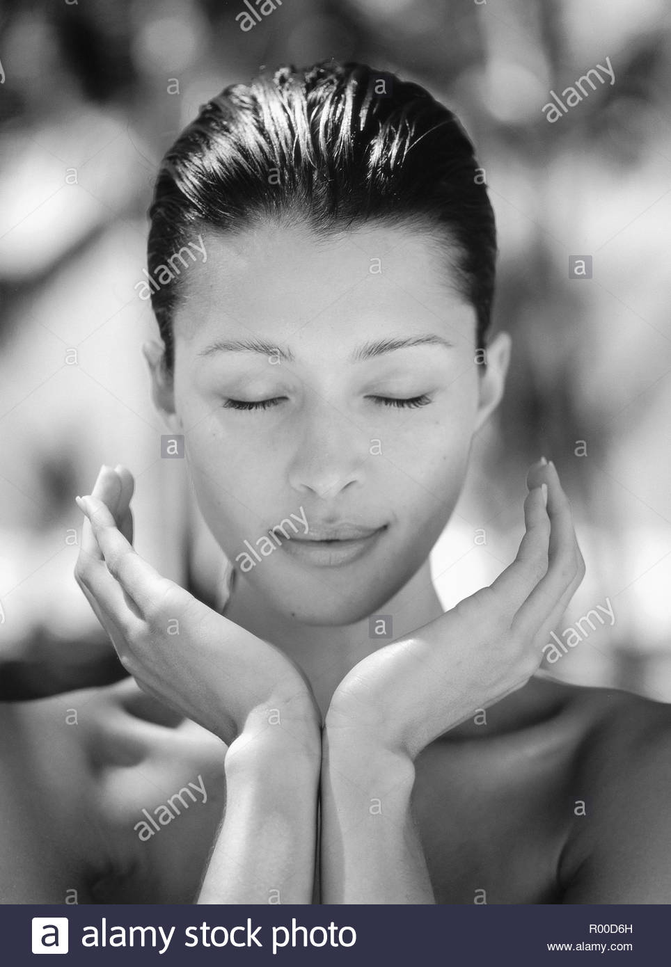Young woman with her eyes closed and hands cupped - Stock Image