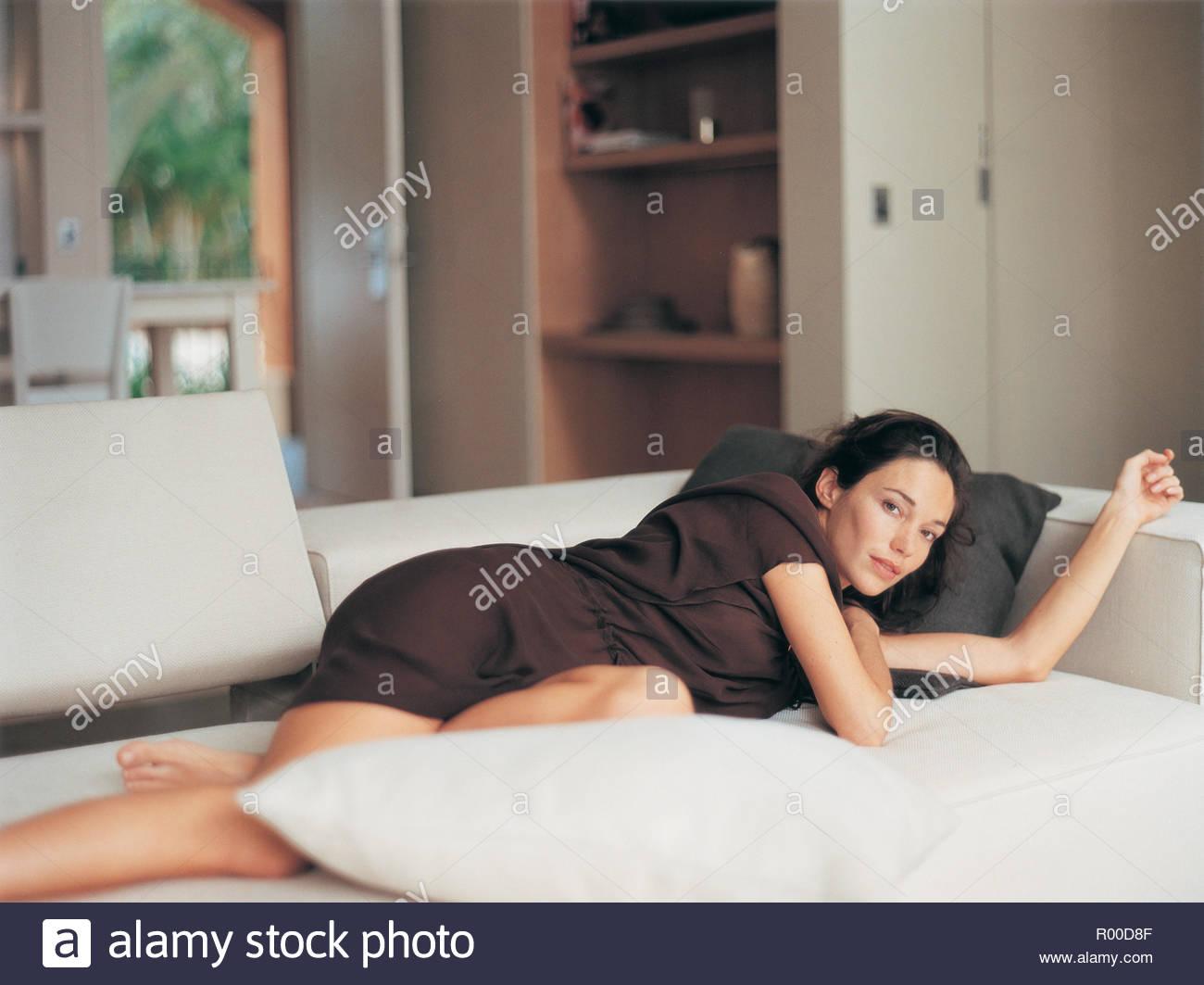 Woman wearing brown dress lying on sofa bed - Stock Image