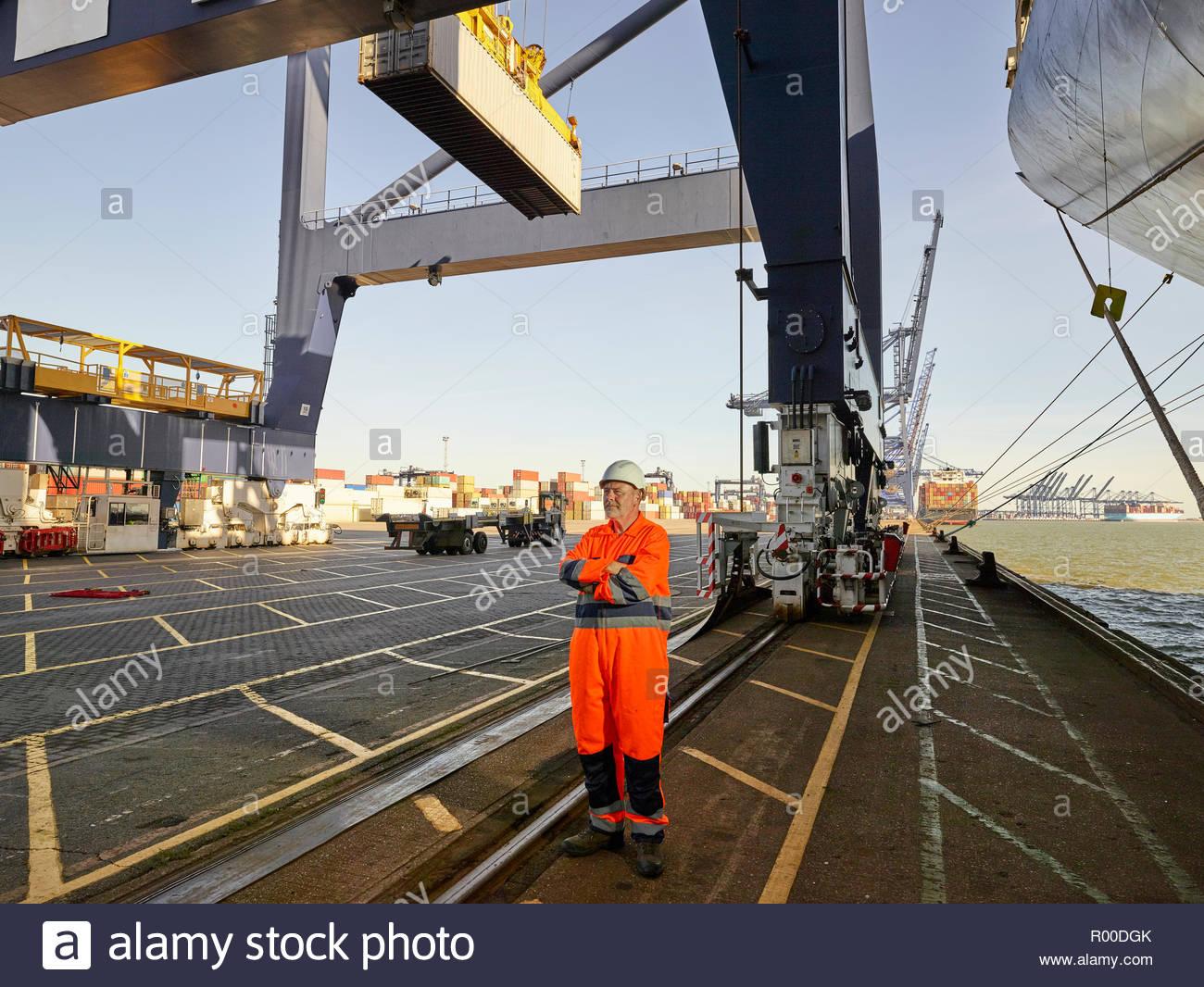 Dock worker in orange jumpsuit at Port of Felixstowe, England - Stock Image