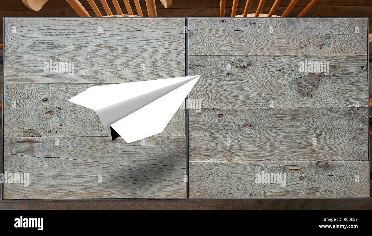 Paper plane origami flying over textured wooden table Stock Photo