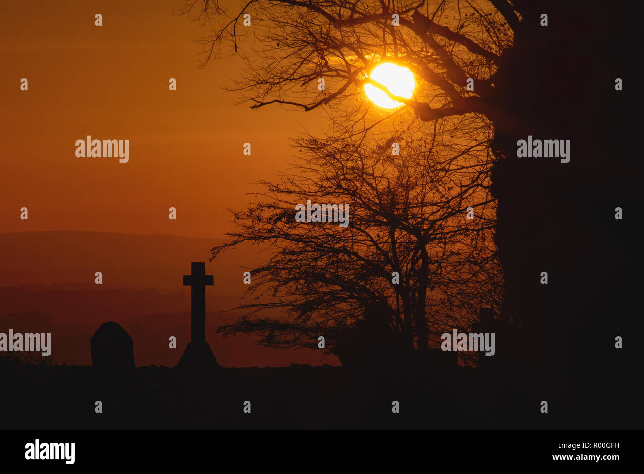 teh sun setting on lanssown cemetary in Bath with the cross and tree silhoutted Stock Photo