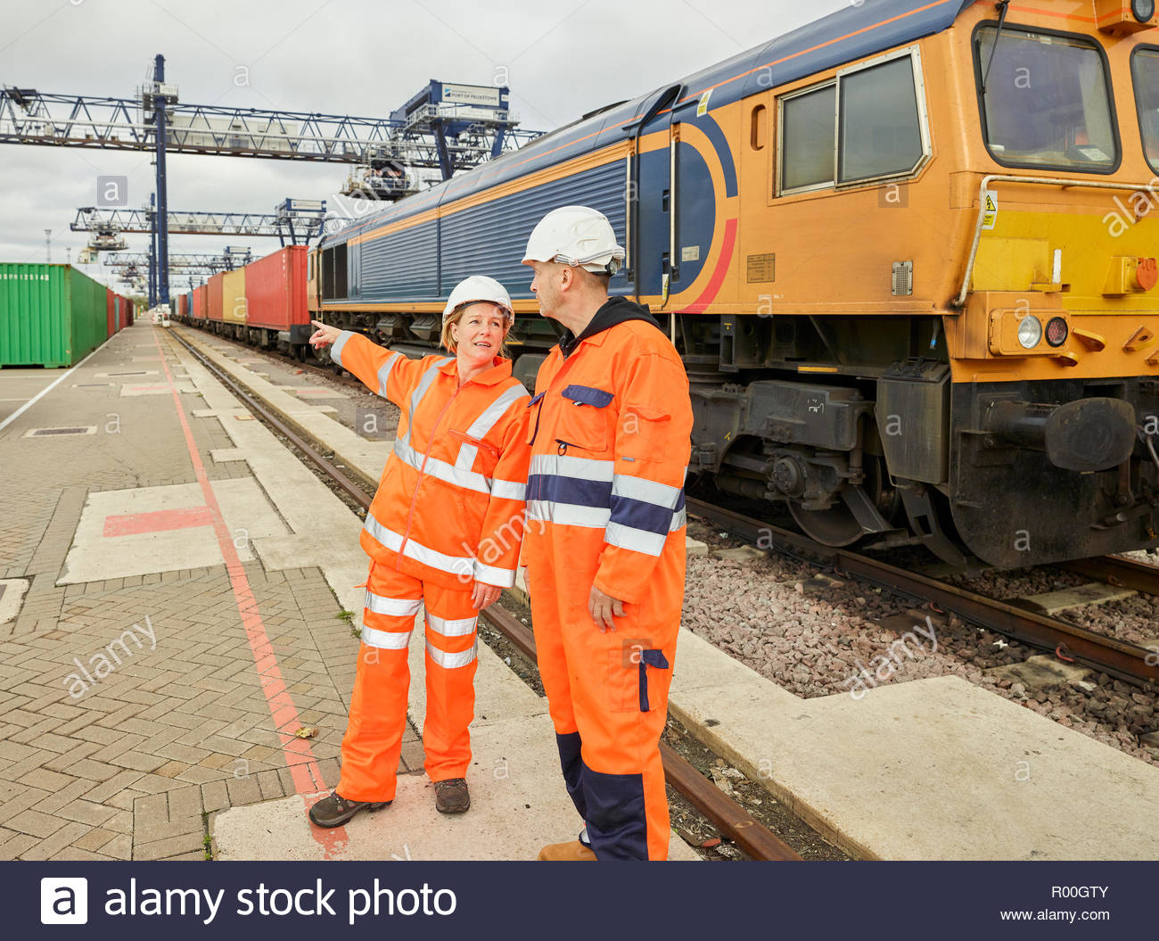 Dock manager advising dock worder loading cargo to train - Stock Image