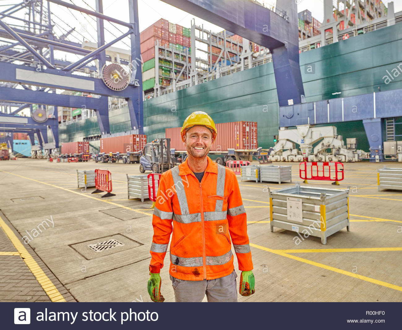 Smiling dock worker in reflective clothing and hard hat - Stock Image