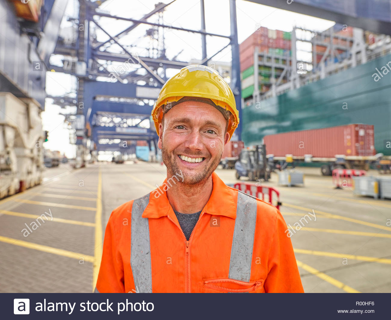 Smiling dock worker in reflective clothing and hard hat infront of container ship and cranes portrait - Stock Image
