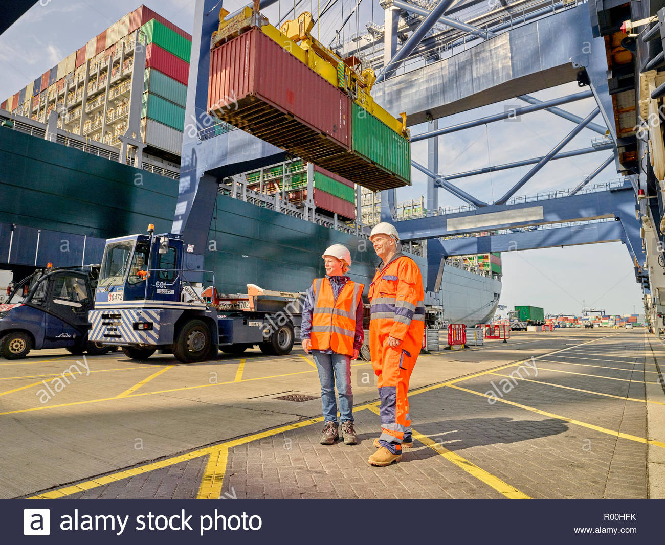 Dock workers by crane lowering cargo container onto truck Stock Photo