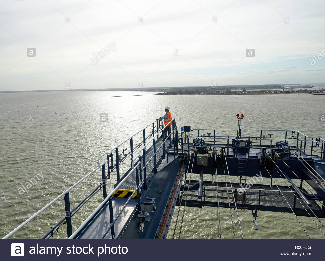 Dock supervisor at the end of crane above cargo ship and container looking out to sea Stock Photo