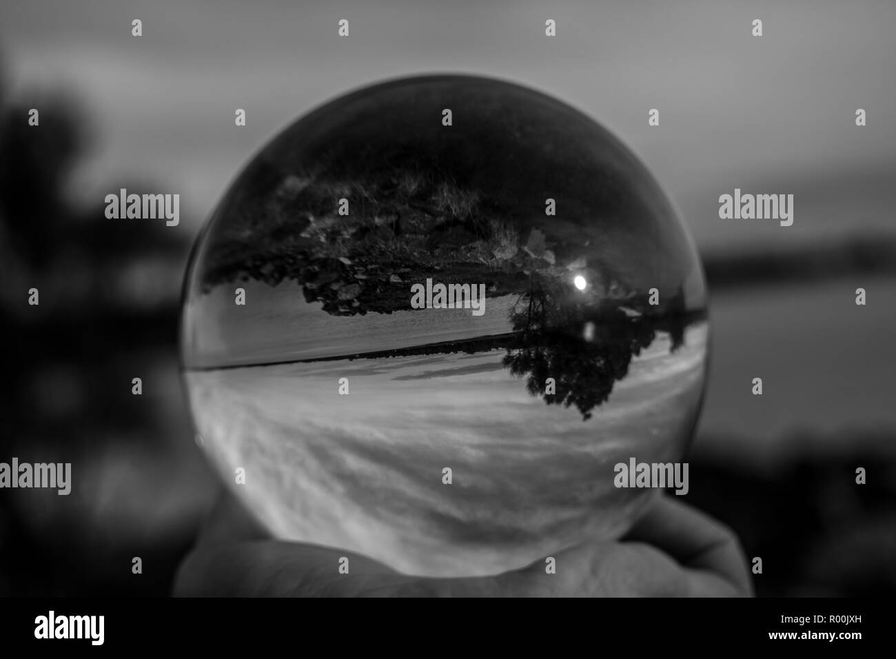 Glass ball sphere in black and white outdoors - Stock Image