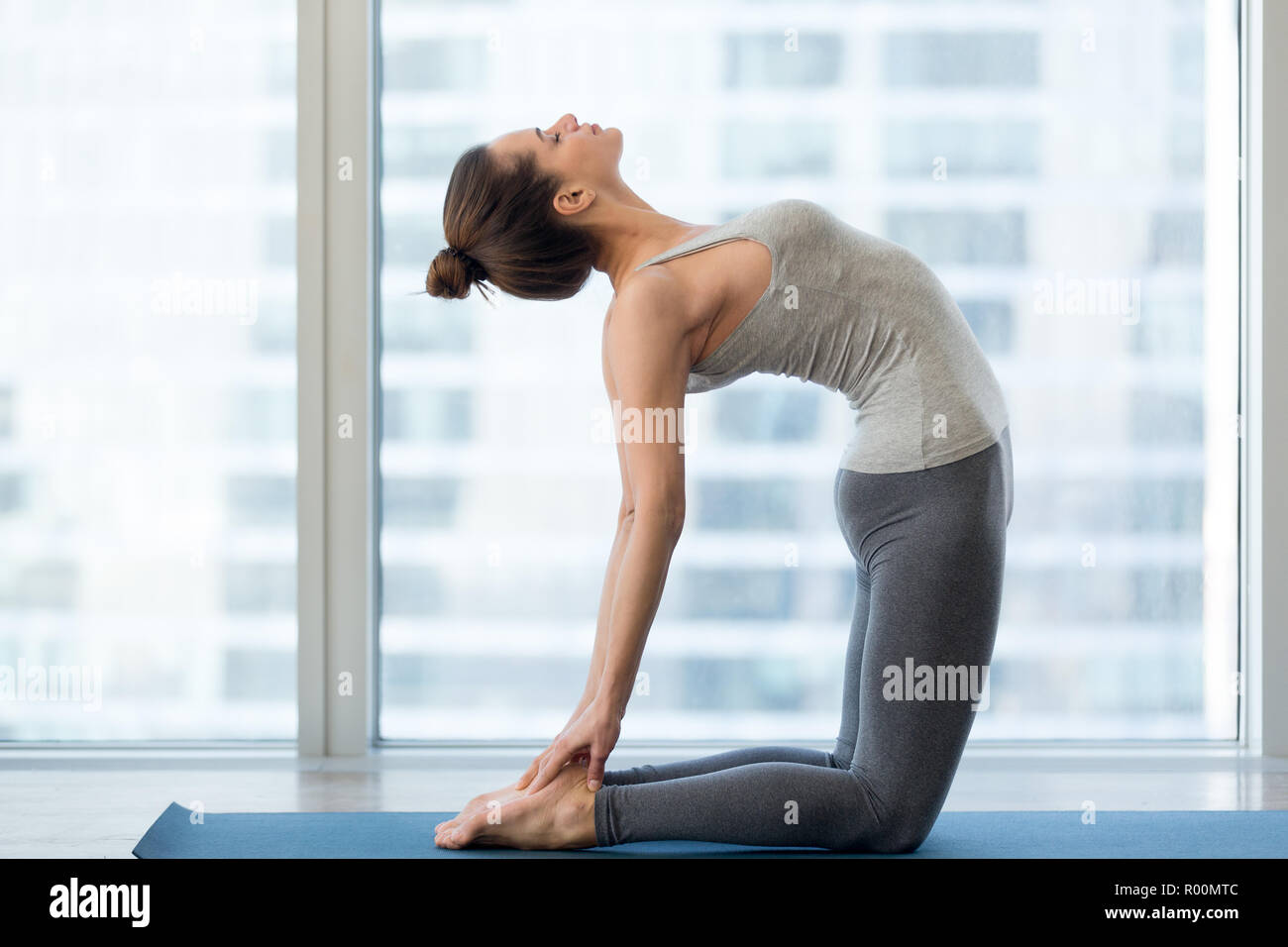 Young sporty woman practicing yoga, doing Ustrasana exercise, Camel pose, working out, wearing sportswear, grey pants and top, indoor full length, yog - Stock Image