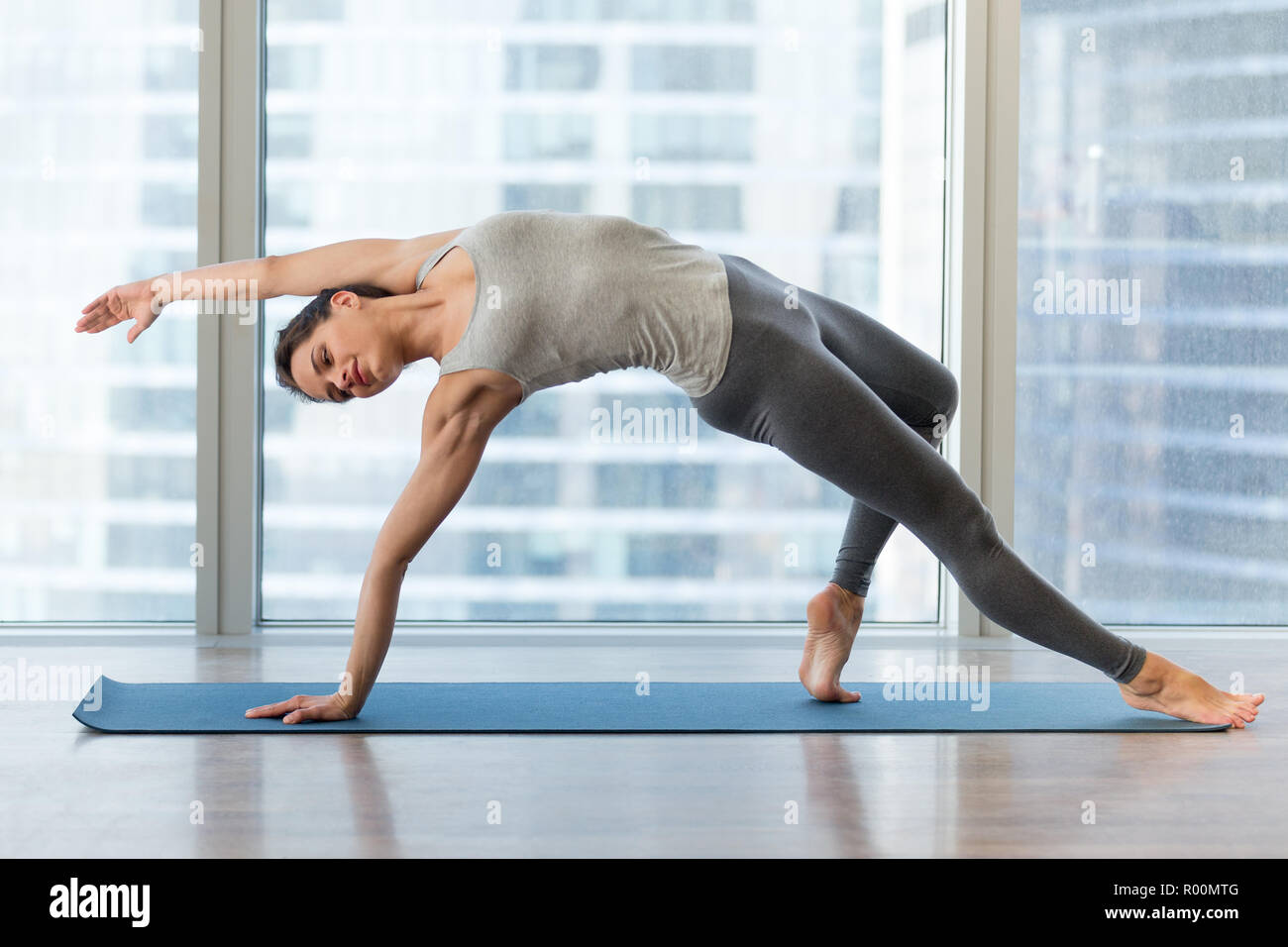 Young sporty woman doing yoga, Wild Thing pose, Flip-the-Dog