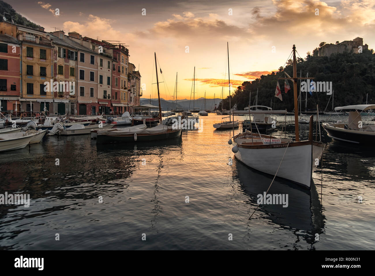 Scenic sunset over the harbour Portofino on the Italian Riviera with colorful ornage sky reflected on the water and moored sailboats and fishing boats - Stock Image