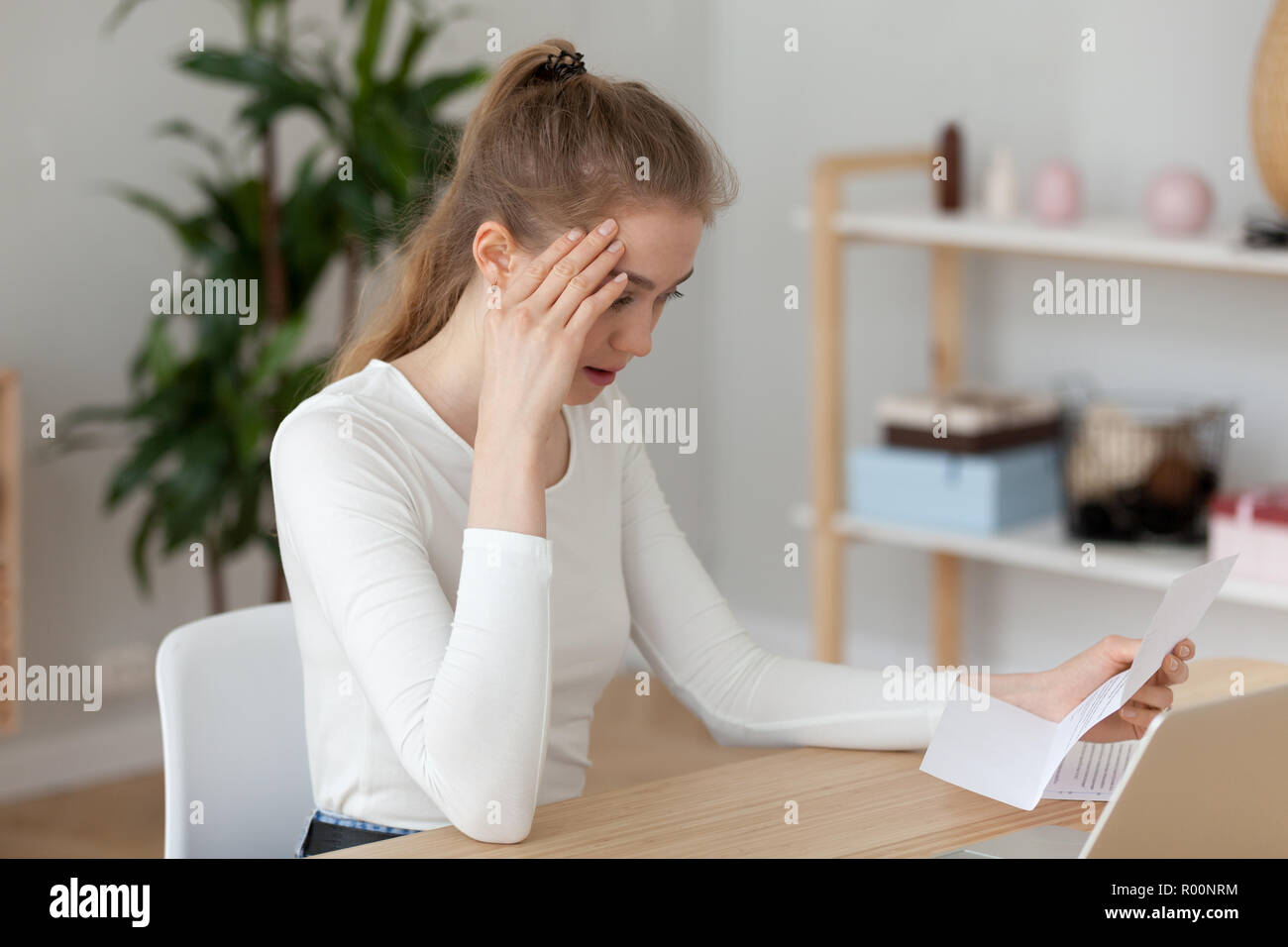 Frustrated girl read unpleasant letter sitting at the desk - Stock Image