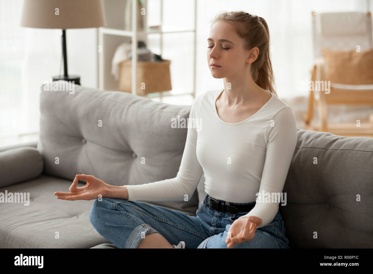 Woman meditating sitting on couch at home - Stock Image