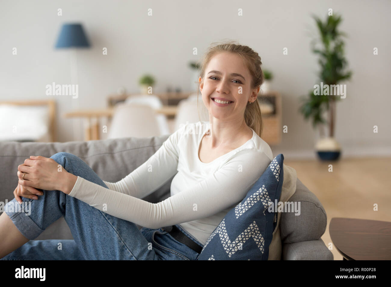 Happy young woman sitting on couch at home - Stock Image