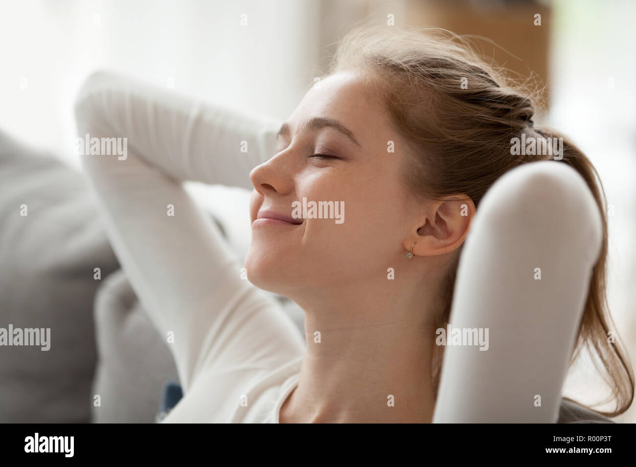 Portrait of young positive woman relaxing at home Stock Photo