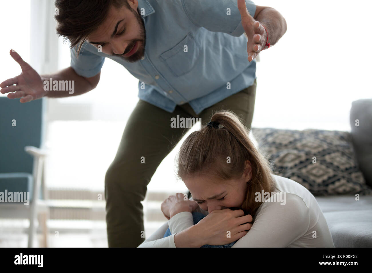 Angry man and frightened woman at home - Stock Image