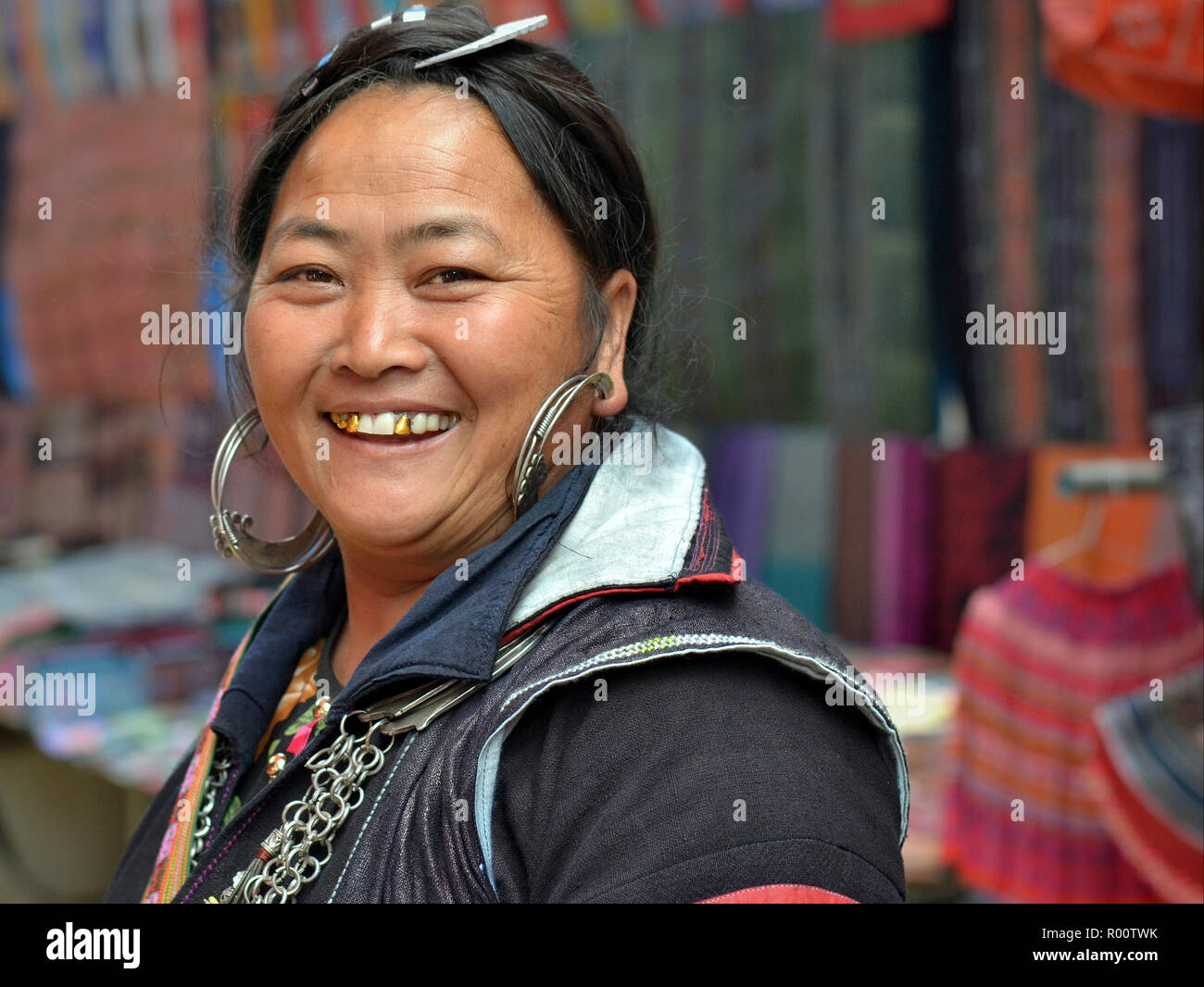 Full-figured, middle-aged Vietnamese Black H'mong hill-tribe woman with large silver earrings and three gold teeth smiles for the camera. - Stock Image