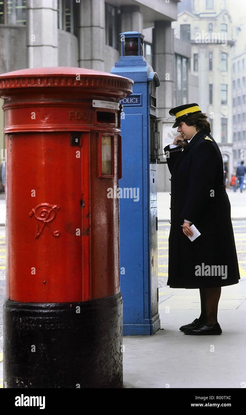 A traffic warden using a Police blue phone box. London, England, UK. Circa 1980's - Stock Image