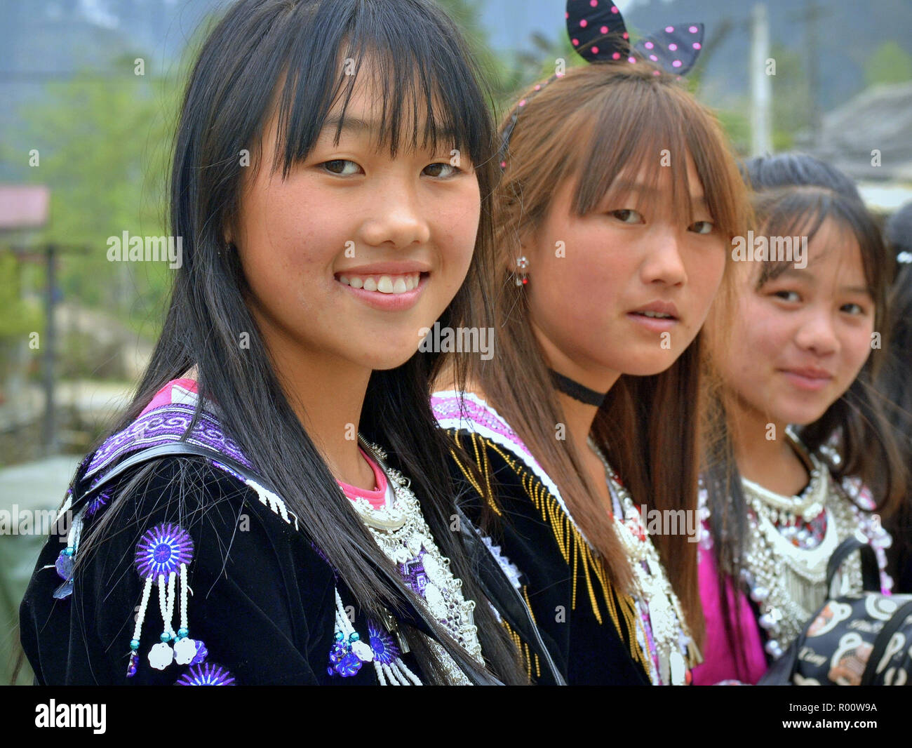 Three Vietnamese Black H'mong hill-tribe teenage girls in traditional attire. Stock Photo