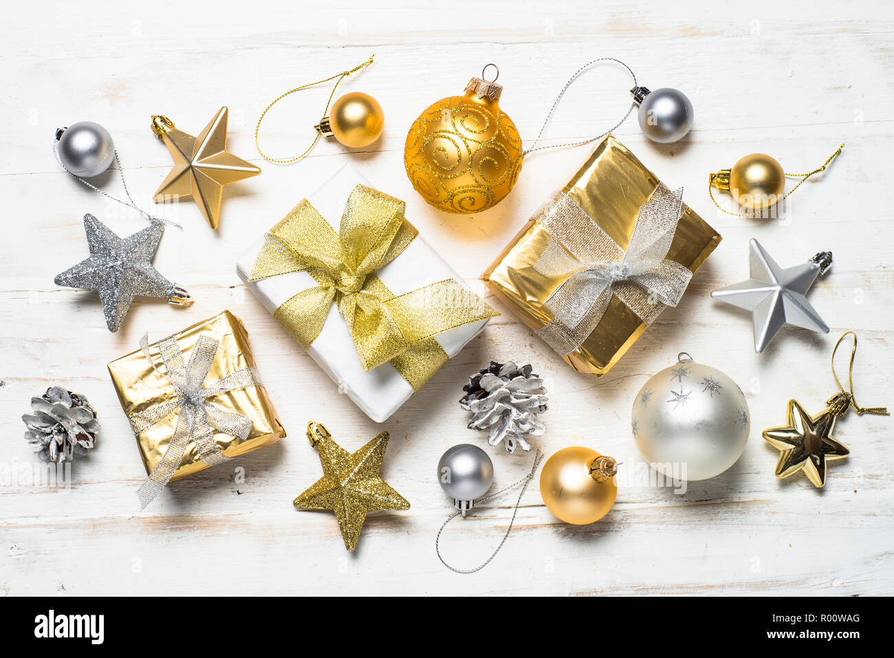 25374fb17c6b Gold and silver christmas present box and decorations on white wooden  background. Top view.