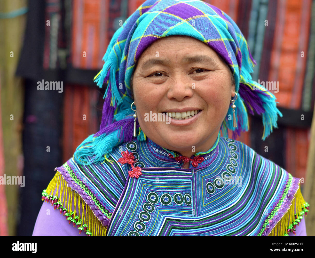 Middle-aged Vietnamese Flower H'mong ethnic-minority hill-tribe woman wears embroidered Flower H'mong traditional attire in blue. - Stock Image