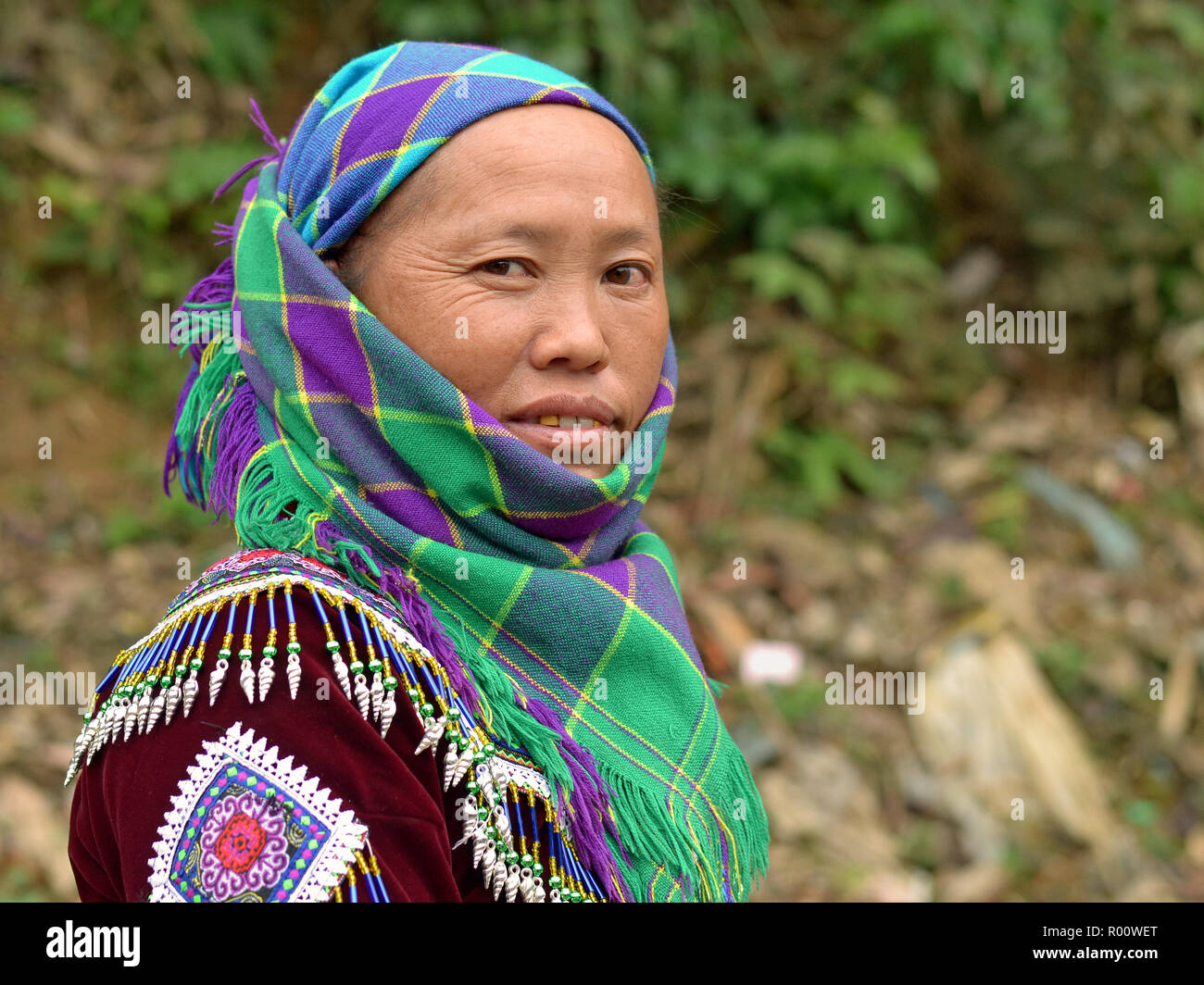 Middle-aged Vietnamese H'mong ethnic-minority hill-tribe woman with two gold teeth wears embroidered traditional H'mong attire and a headscarf. - Stock Image