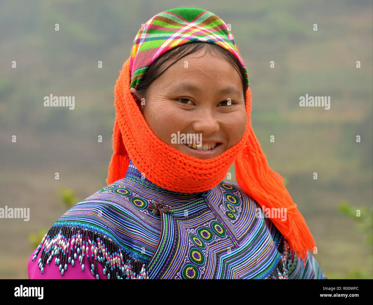 Young Vietnamese H'mong ethnic-minority hill-tribe woman with a gold tooth wears orange shawl and embroidered traditional H'mong attire in blue. - Stock Image