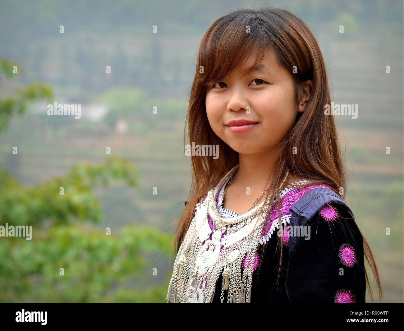 Pretty Vietnamese H'mong teenage girl wears her clan's traditional outfit: embroidered black H'mong blouse with silver tribal necklace. - Stock Image
