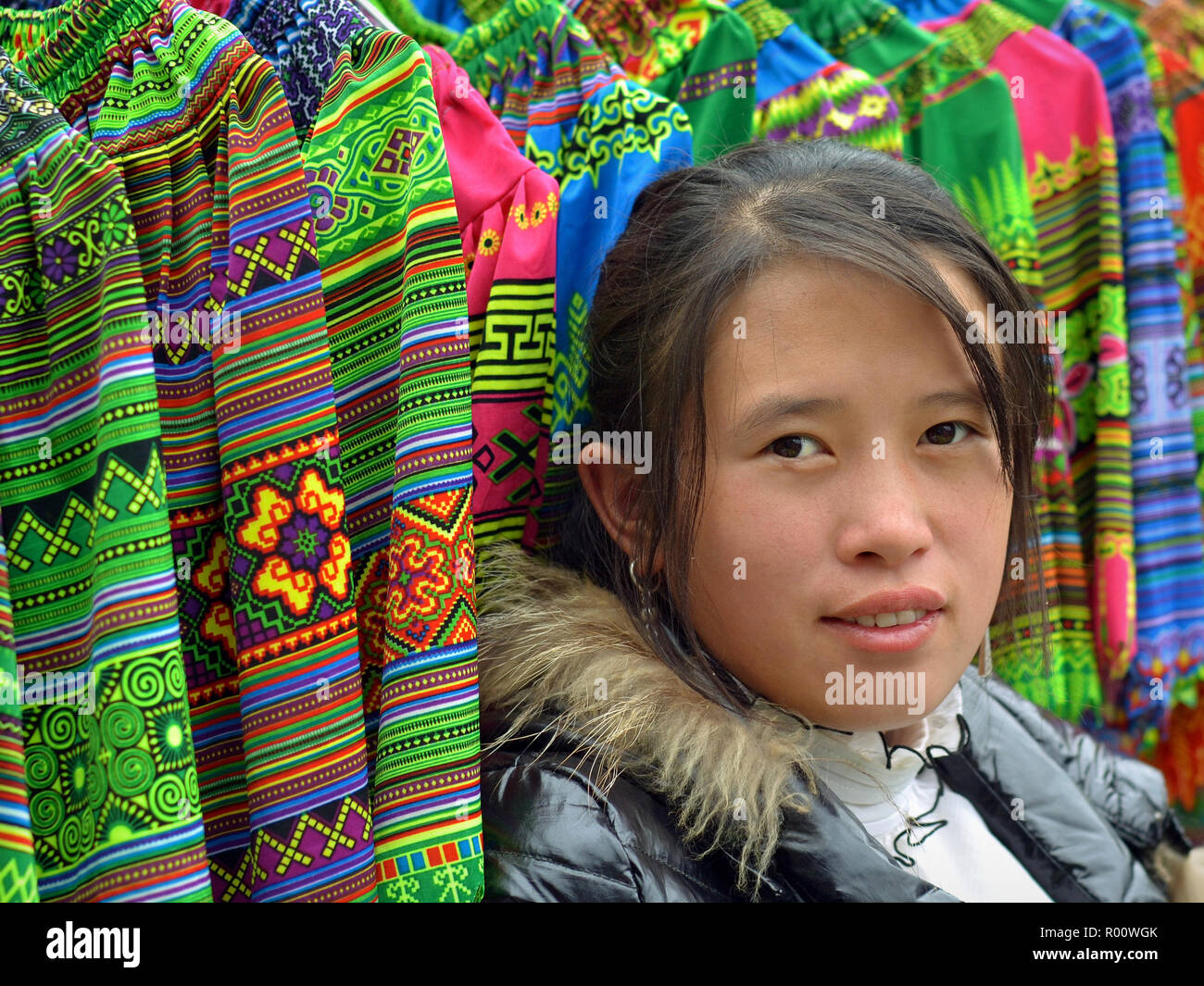 Young Vietnamese H'mong ethnic-minority hill-tribe saleswoman poses for the camera in front of her merchandise (embroidered traditional skirts). - Stock Image