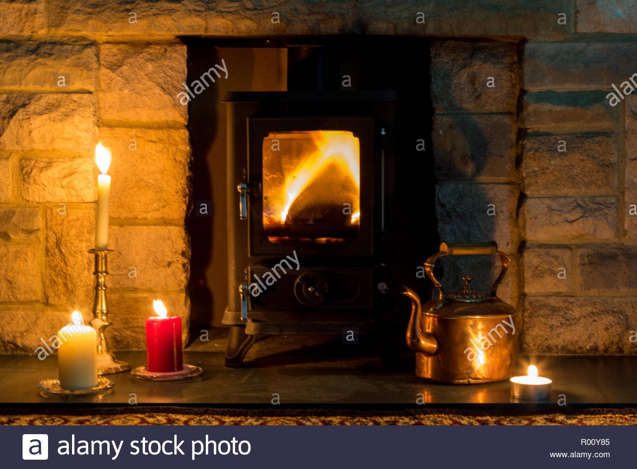 Hygge concept, a log burner, candles, and a copper kettle in a stone fireplace - Stock Image