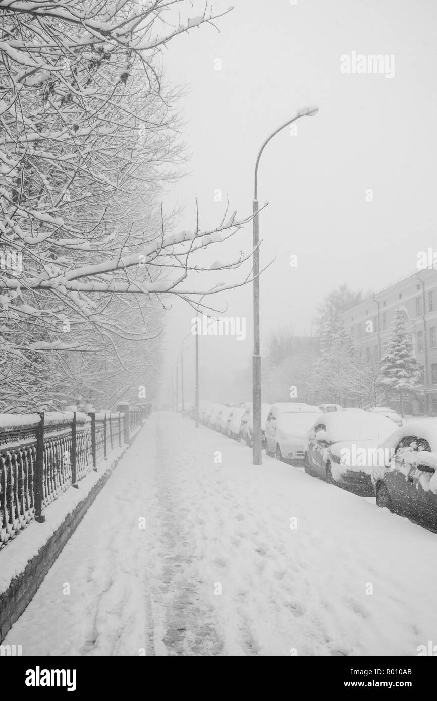Snow-covered sidewalk and parked cars along it during strong snowfall. - Stock Image