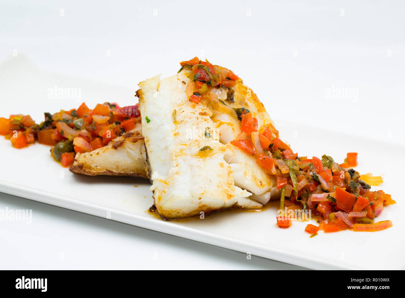 A homecooked pollack fillet, Pollachius pollachius, that has been pan fried and served with peppers, onions, tomatoes and capers. The pollack was caug - Stock Image