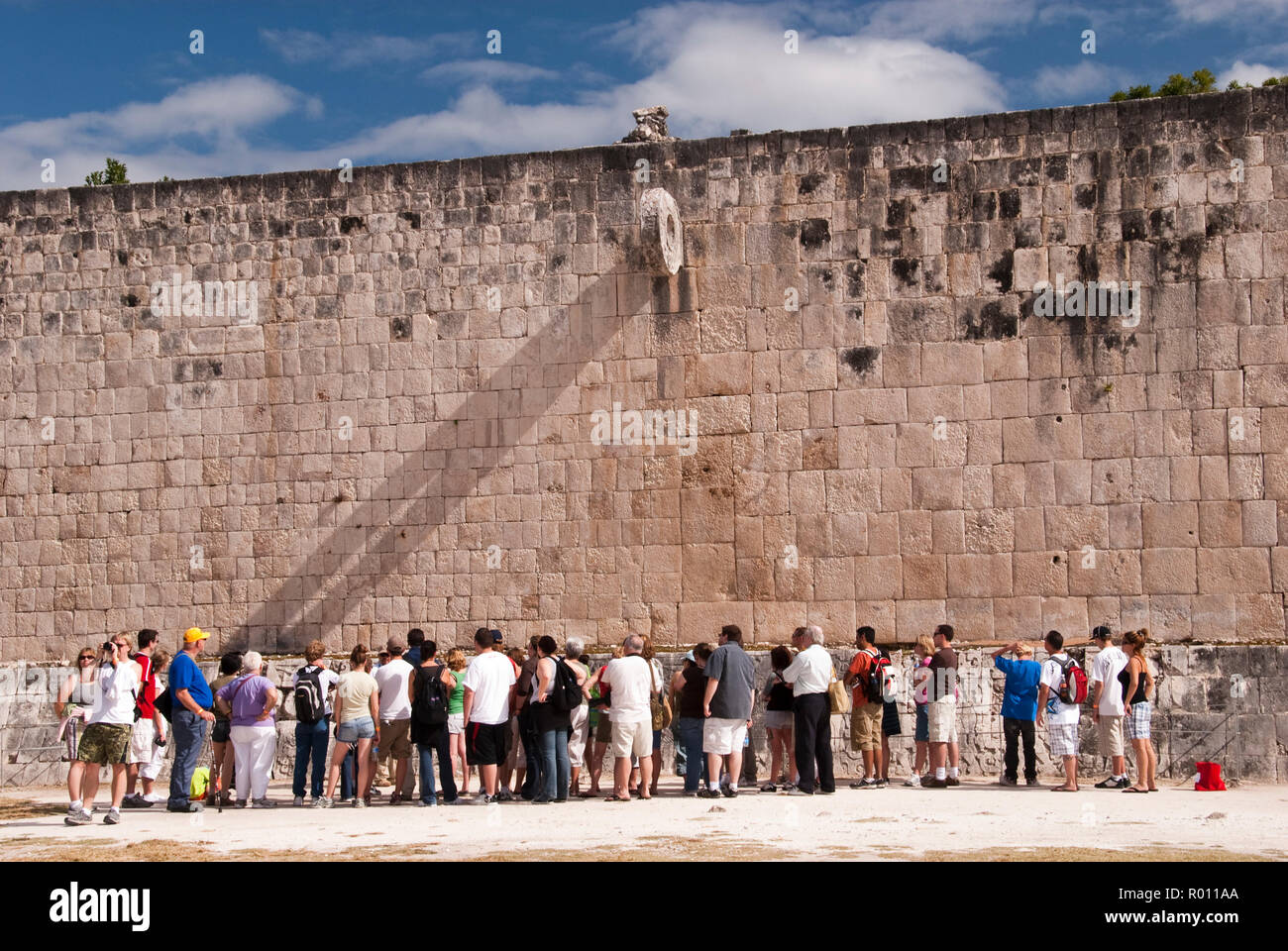 Tourists view the Great Ball Court (Gran Juego de Pelota), used to play a Mesoamerican ballgame, at Chichen Itza, Yucatan, Mexico. - Stock Image