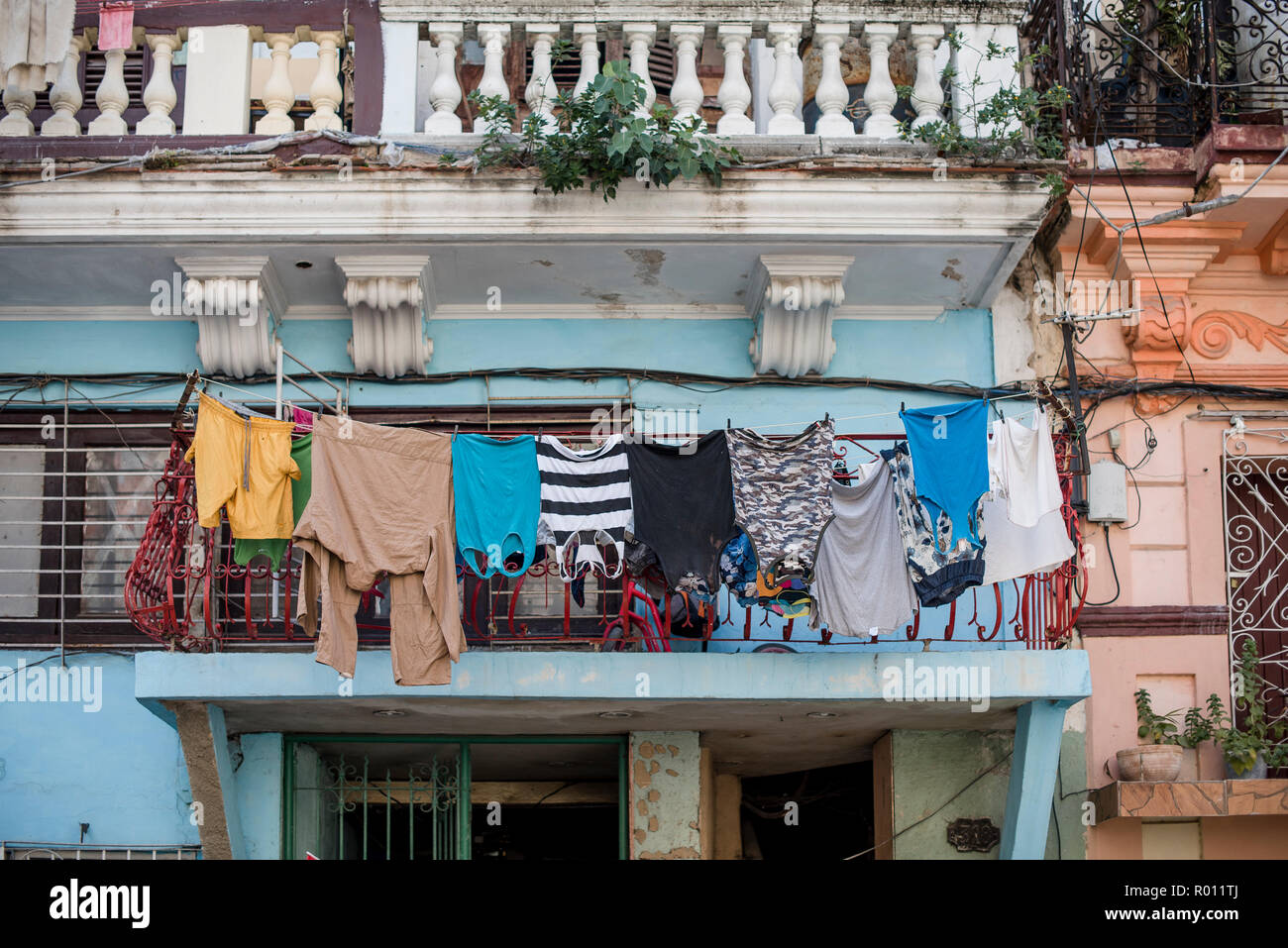 Colorful shirts and pants hang on a clothesline to dry in Havana, Cuba. - Stock Image