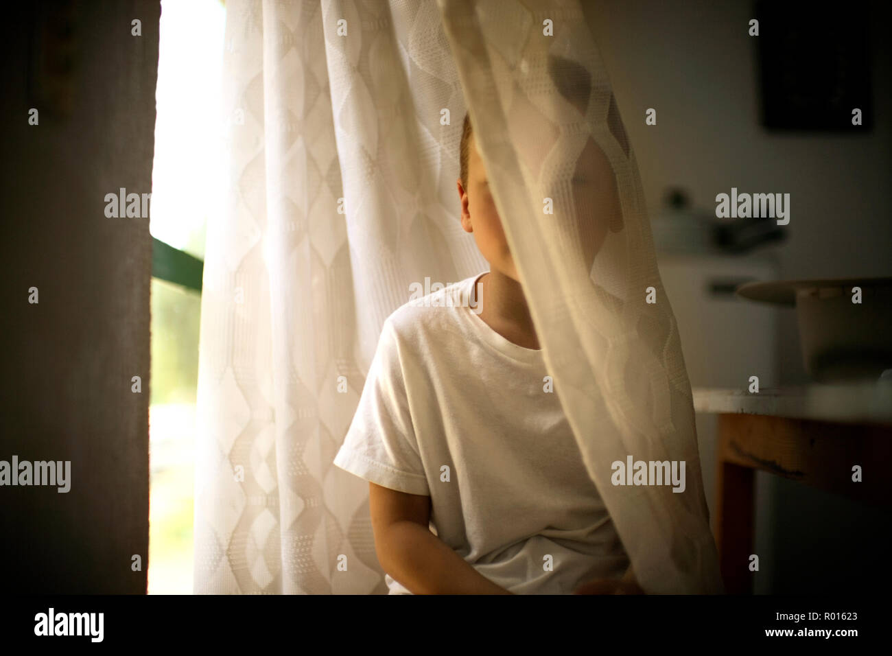 View of a small boy hiding behind a curtain. - Stock Image
