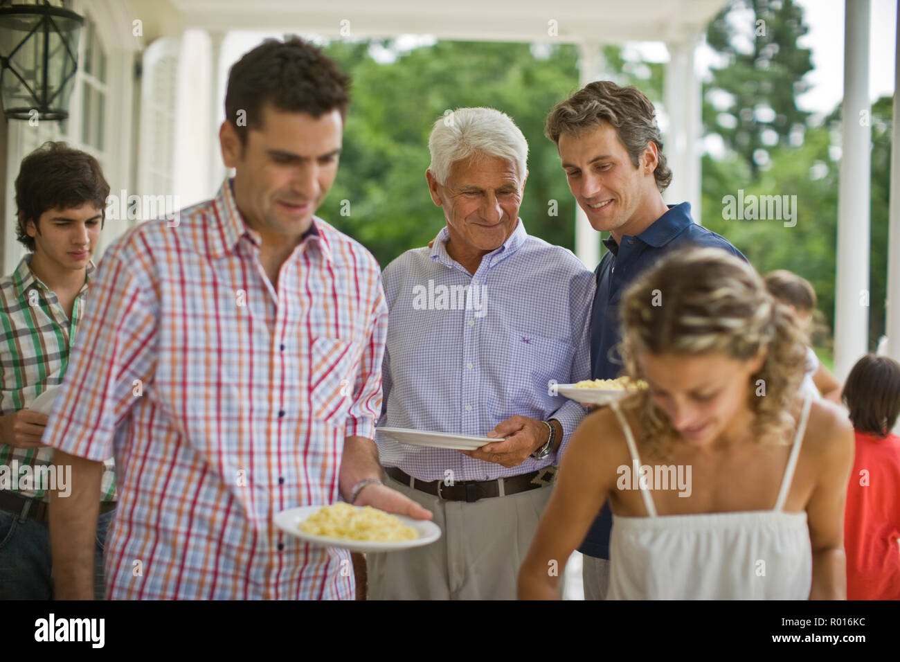 Senior adult man standing with his mid-adult son waiting to get some pasta while his family dish up dinner. - Stock Image
