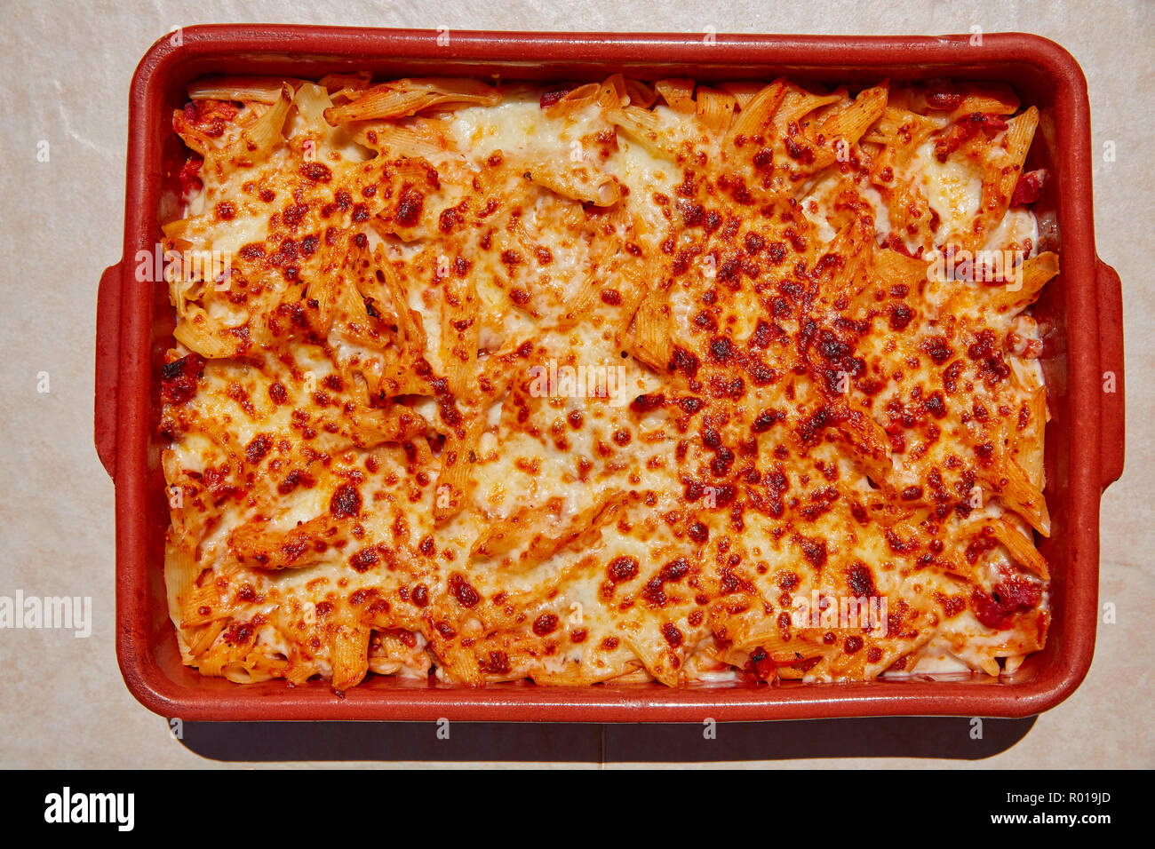 Bolognese macaroni gratinated with cheese in a clay pot - Stock Image
