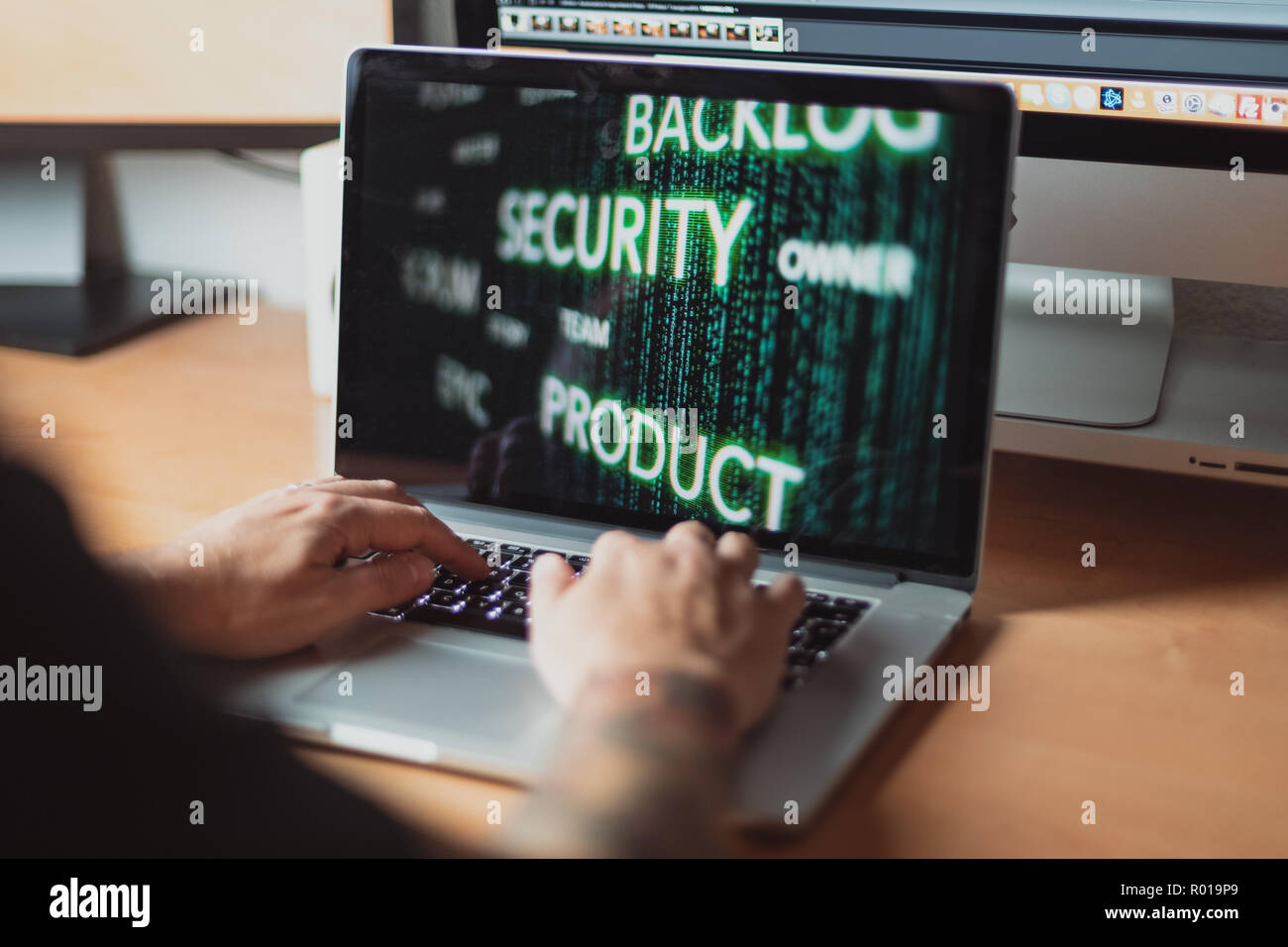Man working on laptop for agile scrum process security concept, wooden table - Stock Image