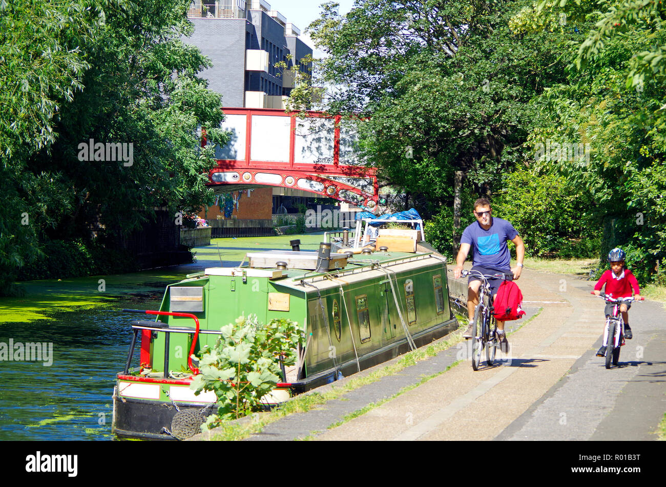 Father and son bicycling along the towpath of the Grand Union canal near the Harrow Road bridge, London . - Stock Image